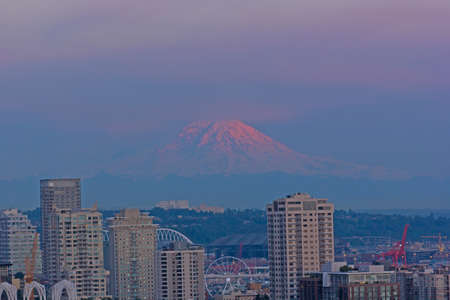 Famous mountain in pastel hues of skies is lit by sunlight. Urban Seattle panorama and Mount Rainier on horizon at sunset, Washington, USA.