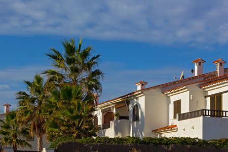 A row of Mediterranean beach summer cottages under blue sky. Palm trees and painted in white houses with tiled roofs.