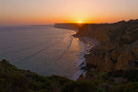 Sun goes down over a distant cliff at sunset in Lagos, Portugal. Panoramic view of the ocean coastline at sunset.