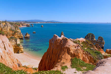 A secluded sandy beach in the morning. Panorama with scenic cliffs and quiet waters of sea harbor in Lagos, Portugal. Фото со стока