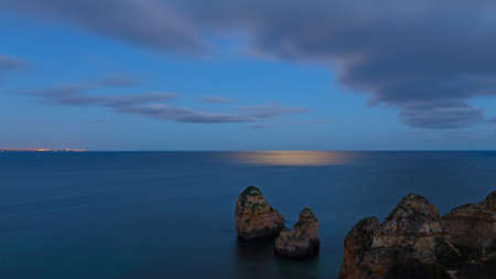 Moonlight shines on a calm surface of Atlantic Ocean. Panorama with distant town at night and horizon over the water, Algarve, Portugal. Фото со стока
