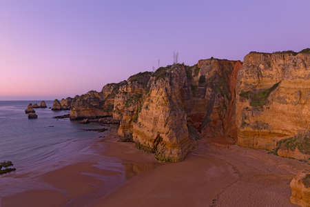 Empty sandy beach with whimsy cliffs at sunrise in Lagos, Portugal. Cloudy sunrise over the Atlantic Ocean.