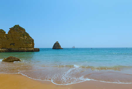 Sailing in safe waters of ocean harbor near Lagos, Portugal. Sandy beach and coastal line panorama on a spring morning. Фото со стока