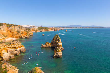 Sport activities in safe waters of ocean harbor in Lagos, Portugal. Coastline panorama on a spring morning with sandy beaches, cliffs and pristine waters.