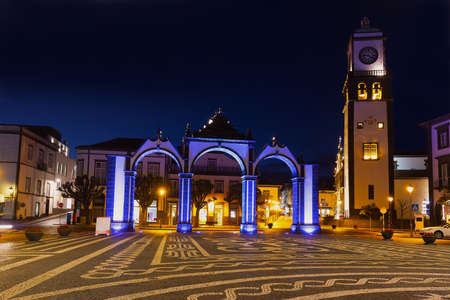Night scene of Ponta Delgada main square with Portas da Cidade - City Gate and Saint Sabastian church on Azores, Portugal. The church with clock tower and the historic gate illuminated at night.