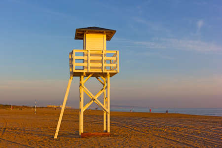 A lifeguard cabin on a sandy beach at sunrise. Mediterranean Sea beach in Valencia region of Spain.