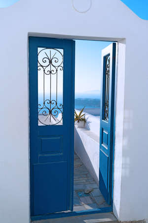 Blue door opened to a terrace with sea views.