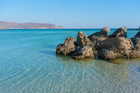 Vacationers enjoy warm shallow waters on a coast of Crete island in Greece. Фото со стока