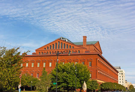 National Building Museum in Washington DC, USA. The building in early autumn with deciduous trees around its perimeter. Редакционное