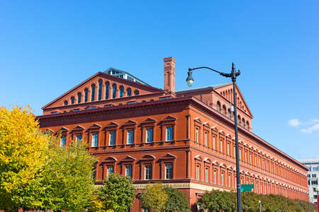 An example of Italian Renaissance Revival architecture in National Building Museum structure in Washington DC. The building in early autumn with deciduous trees around its perimeter. Редакционное