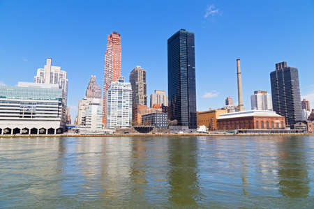 Manhattan skyline in the morning near East River waterfront in New York, USA. Urban landscape with river view and bright blue skies. Фото со стока