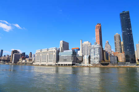 Manhattan skyline in the morning as seen from Roosevelt Island in New York, USA. Urban landscape with river view and bright blue skies. Imagens