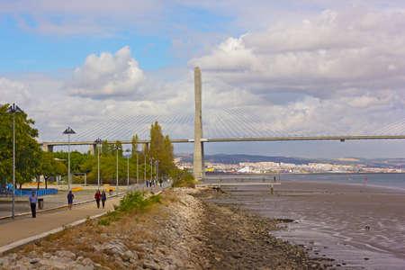LISBON, PORTUGAL – OCTOBER 16, 2019: Vasco da Gama bridge and pedestrian walkway along Tagus River with the capital city on horizon.