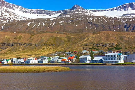 Landscape of coastal town in Northern Iceland during spring. Mountain tops covered in snow, while waterfalls located beneath them rushing towards the sea waters.