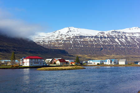 Houses in sea harbor of Norther Iceland with snowy mountains nearby. Inhabitable Icelandic landscape in springtime.