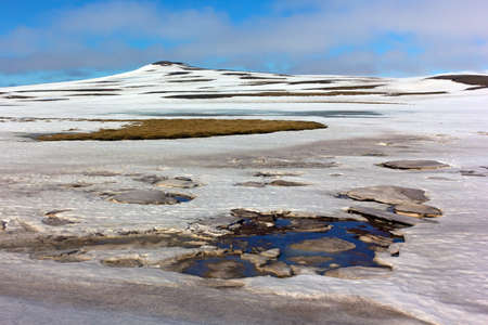 Mossy fields under snow in Northern Iceland during springtime. Panorama with snow, water and mountains. Imagens