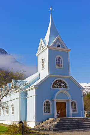 Scenic wooden church painted in blue color against mountainous landscape in Northern Iceland. Icelandic traditional official building structure with framed windows and decorative bits of adornment. Imagens