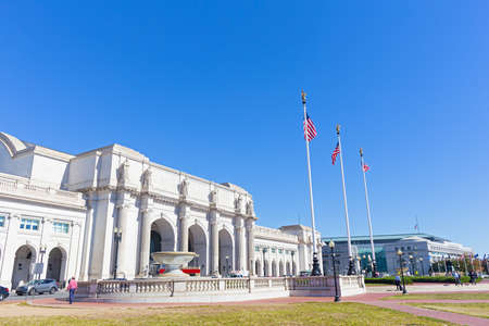 A square in front of the Union Station Building in Washington DC, USA. Facade of the Union Station Building with marble statues on top of columns on a sunny afternoon.