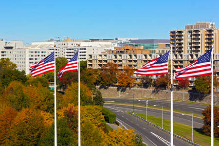 Bright colors in landscape of Washington DC, USA. Downtown on sunny day in autumn with trees foliage and national flags on high poles. Stok Fotoğraf