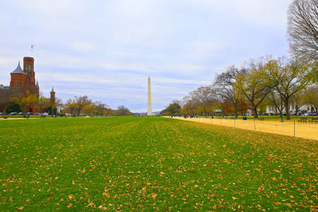 National Mall in autumn with the Washington Monument at distance in Washington DC, USA. The National Mall landscape with empty benches and historic buildings on both sides under cloudy skies. Stok Fotoğraf