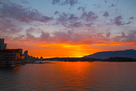 Spectacular sunset over Vancouver city harbor in Brithish Columbia, Canada. Scenic landscape litten by sunset with mountains chain at horison.