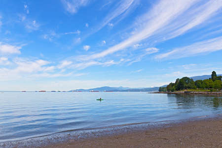Panoramic view of English Bay with horizon over water and mountains, Vancouver, British Columbia, Canada. Kayak, seagulls, nautical vessels and snow mountain peaks in bay landscape on a sunny day. Stok Fotoğraf