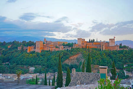 City landscape with ancient Arabic fortress and Sierra Nevada mountains on horizon. Stok Fotoğraf