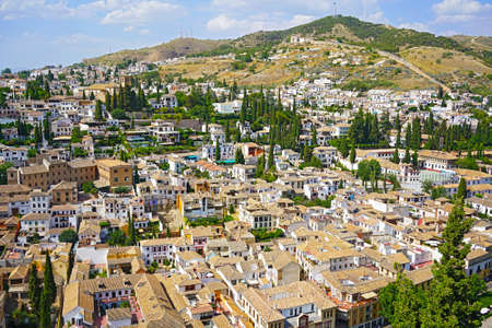 Panoramic view on Granada city suburbs and mountains on horizon from the castle, Spain.