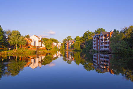 Suburban neighborhood of Washington DC in early autumn. Houses with reflection in a pond surrounded by trees and shrubs. Stok Fotoğraf