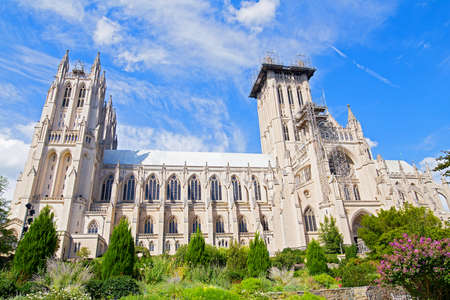 National Cathedral and gardens of Washington DC, USA. Gothic building surrounded by gardens under blue sky with cloud on a sunny day in spring.