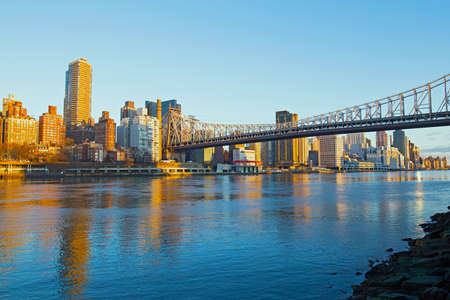 Sunrise over Manhattan in New York City, USA. Skyline illuminated by rising sun with reflection in river.