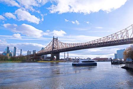 East River landscape in New York City near Roosevelt Island. Ferry motorboat brings passengers on island in early winter morning. Stok Fotoğraf