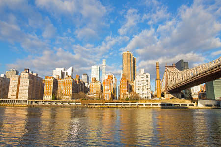 New York City skyline in the morning with sun beaming into windows of Manhattan buildings, USA.
