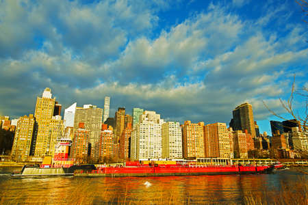 A view on Manhattan from Roosevelt Island in New York, USA. Waterfront buildings illuminated by sunrise under blue sky with cumulus clouds.