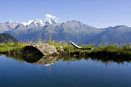 Breathtaking scene of Alpine lake with relax chair. Snowy mountains in background
