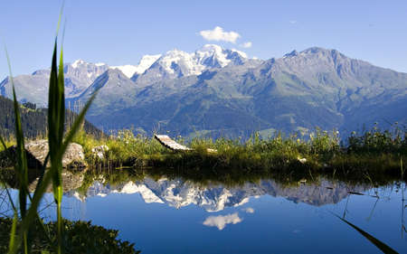 Breathtaking scene of Alpine lake with relax chair. Snowy mountains in background 2 Stock Photo