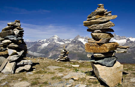Stones pile in front of Swiss snowy mountains