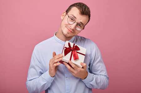 A surprised man in blue shirt with black glasses holds a gift in a box with lid and red bow in his hands, looking straight. Holiday, happiness. Give a present. Guy bowed his head. Focus on gift.
