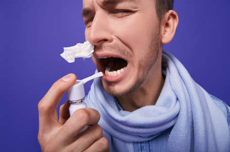 An ill guy with blond hair in a denim shirt, blue scarf around his throat is standing with inhaler and napkin in his nose on a blue background.