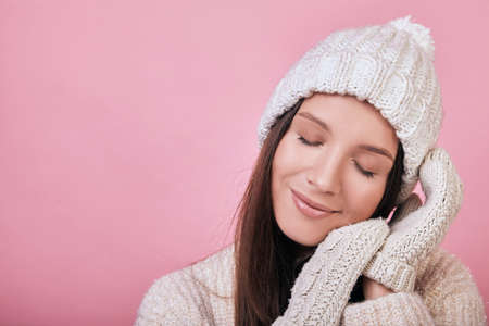 Cute girl with closed eyes in a knitted milky gray sweater and hat stands on the background. The atmosphere is cozy, warm in cold weather. As if sleeping on her hands in mittens.