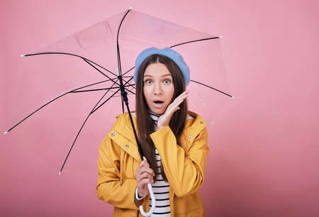 Pretty surprised girl in a gentle blue barret, a striped blouse and a yellow rain jacket smiles cute against a pink background with umbrella in hand. Arm near her face, looking forward with open mouth