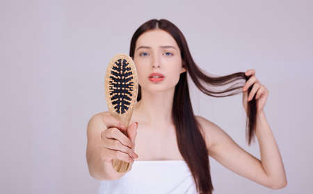 A well-groomed brunette, wrapped in a white bath towel, holds a wooden comb in her hand. Hair care, spa, hydration and volume for hair. Hair loss. Banque d'images - 134030042