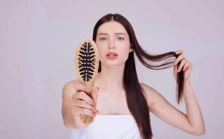 Eine gepflegte Brünette, in ein weißes Badetuch gehüllt, hält einen Holzkamm in der Hand. Haarpflege, Spa, Feuchtigkeit und Volumen für das Haar. Haarverlust.