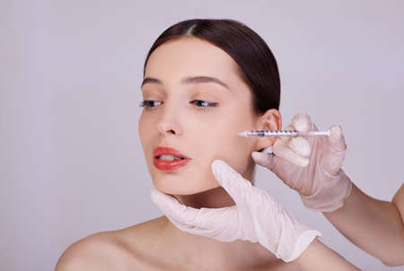 A cosmetologist makes anti-aging procedures for face injections to tighten and smooth wrinkles on the face skin of a beautiful, young woman in a beauty salon. Cosmetology.