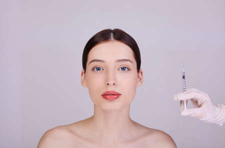 Beautician injections for the face to tighten and smooth wrinkles on the skin of a well-groomed young woman. Holds a syringe near the face of the model. Cosmetic skin care.