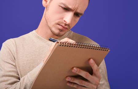 Concentrated author writes an action plan or solves a problem in a paper notebook . Redactor stands on purple background in a beige sweater and enthusiastically writes a novel or poem. Stock Photo