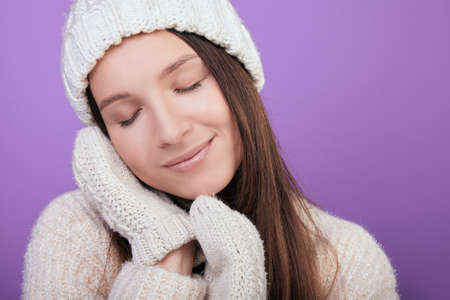 Girl closed eyes and clasped her hands in mittens under her cheek. Winter sleep. Photo of a young girl in a good mood in a warm white sweater and white mittens. Photo on a purple background.