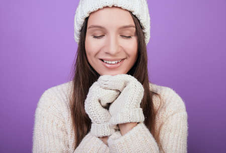 Cute girl in a white knitted hat and white mittens folded her hands under her chin. Looks down, embarrassed, smiling. Photo on a purple background. The atmosphere of comfort.