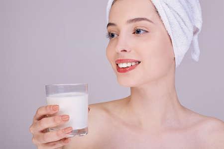 Młoda dziewczyna o zadbanej skórze w białym ręczniku na głowie trzyma w dłoniach szklankę mleka. Odpowiednie odżywianie. Zdrowe zęby. Wapń. Mleko roślinne.
