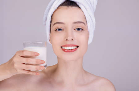 The girl, smiling broadly, with well-groomed skin, in a white towel on her head, is holding a glass of milk in her hands. Proper nutrition. Healthy teeth, calcium. Vegetable milk. Vegan product. Stock fotó